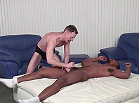 Muscular black gay stud lets a white nerd rub his mighty cock